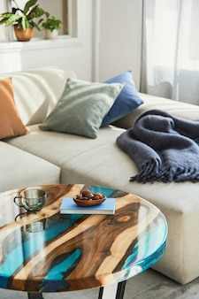 Стильная композиция с дизайнерским журнальным столиком из эпоксидной смолы, диваном, одеялом, подушками, книгой, декором и личными аксессуарами в современном домашнем декоре .. подробности.