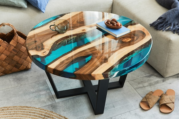 Стильная композиция с дизайнерским журнальным столиком из эпоксидной смолы, диваном, одеялом, подушками, книгой, декором и личными аксессуарами в современном домашнем декоре. шаблон. подробности.