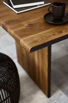 Stylish composition of wooden craft table with design black rattan pouf, mug, book and concrete floor. template.