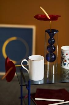 デザインのコーヒーテーブル、マグカップ、本、赤い花が付いたモダンなリビングルームのインテリアのスタイリッシュなコンポジション。閉じる。黄色い壁。テンプレート。
