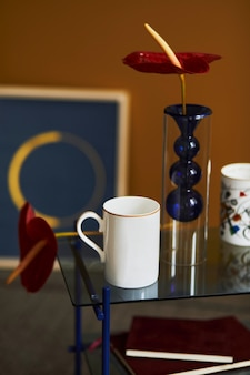 Stylish compositon at modern living room interior with design coffee table, mug, book and red flower. close up. yellow wall. template.
