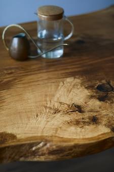 椅子、銅のじょうろ、美しいオレンジ色のモダンな床を備えたクラフトオークの木製テーブルのスタイリッシュな構成。テンプレート。