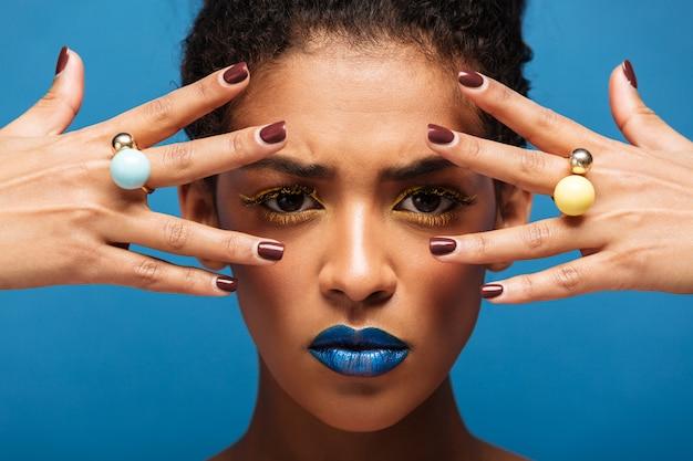Стильная концентрированная афро женщина с ярким макияжем демонстрирует кольца на пальцах, держа руки на лице, изолированном над синей стеной