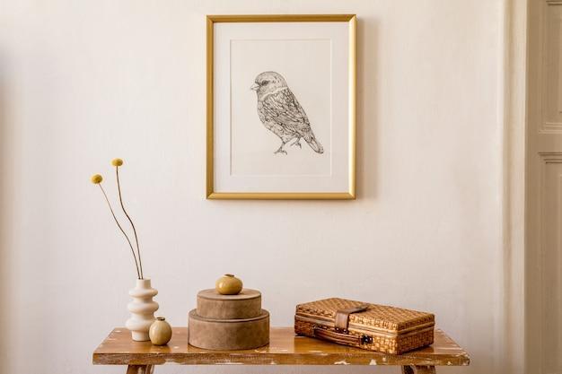 ゴールドのモックアップフレーム、木製のベンチ、ボックス、花瓶のドライフラワー、白い壁、モダンな家の装飾のエレガントなパーソナルアクセサリーを備えたリビングルームのインテリアのスタイリッシュなコンセプト。