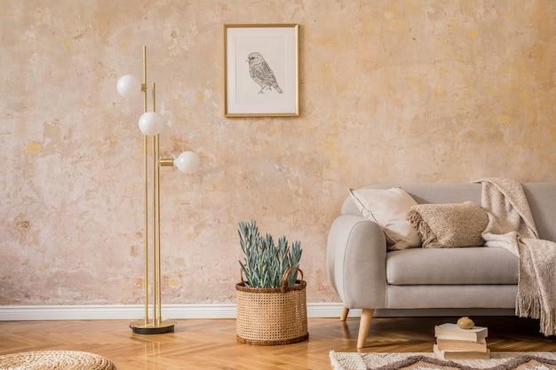 Стильная концепция интерьера гостиной с золотой лампой, дизайнерским серым диваном, макетом фоторамки, книгами, растением, ковром, пуфом из ротанга, подушкой, пледом и элегантными аксессуарами в домашнем декоре.