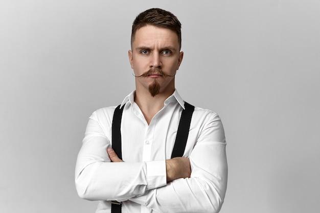 Elegante capo barbuto fiducioso in bretelle e camicia bianca in posa isolato alla parete dello studio copyspace vuoto
