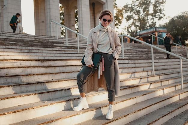 エレガントなスタイルのコートで通りを歩くスタイリッシュな自信を持ってファッショナブルな女性