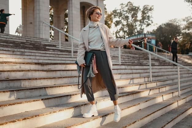Stylish confident fashionable woman walking in street in elegant style coat
