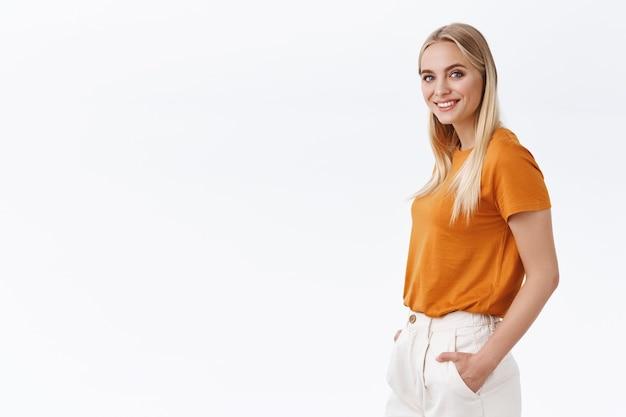 Elegante, sicura collega di bell'aspetto con i capelli biondi, indossa una t-shirt arancione, guarda a metà macchina fotografica sicura di sé, si tiene per mano nei pantaloni, sorride come un professionista, sfondo bianco