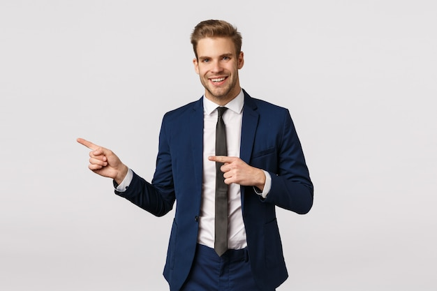 Stylish and confident, handsome blond bearded man in classic blue suit, pointing left, showing business partner place where discuss meeting, invite come inside office, standing white background