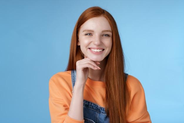 Стильная уверенная в себе счастливая умная креативная рыжая девушка выглядит довольной задумчивой, как интересное предложение, прикоснуться к подбородку улыбается одобрение дружелюбно разговаривает стоя синий фон носить комбинезон