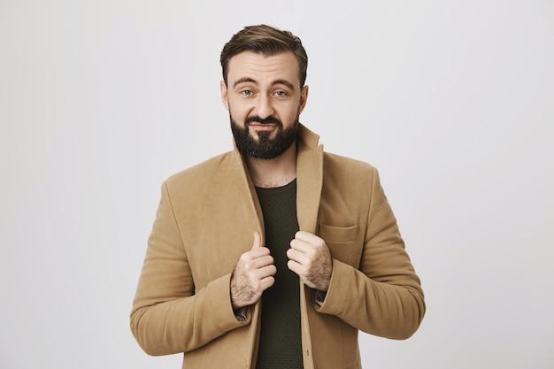 Стильный уверенный в себе мужчина в пальто улыбается
