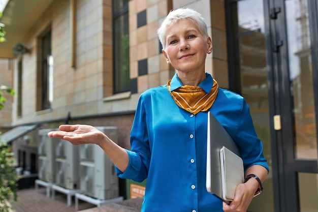 Stylish confident middle aged businesswoman with short hairstyle posing outside office building with laptop under her arm, making gesture as if holding something on hand