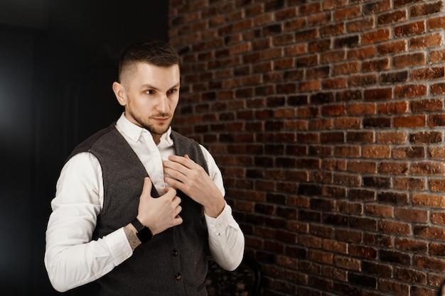 거울을보고 자신을보고 세련 된 자신감 젊은 남자. 상점이나 재봉 스튜디오에서 양복 입기