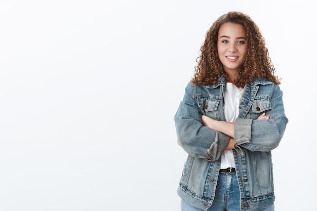 デニムクロスハンドチェストを身に着けているスタイリッシュな自信を持って若いふっくらとした縮れ毛の女の子は、最近のプロジェクトについて話し合う同僚が話している自信のある笑顔を達成しました
