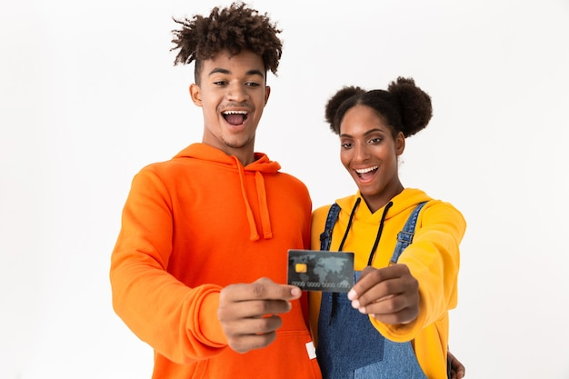 Stylish couple in colorful clothes smiling and holding credit card together, isolated over white wall