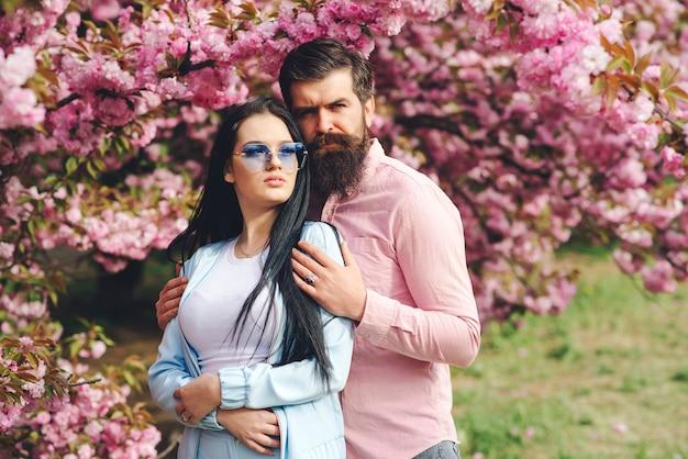 휴가를 즐기는 세련 된 커플. 사랑. 봄 핑크 사쿠라 꽃. 벚꽃이 만발한 정원. 수염 난된 세련 된 남자 여자 친구를 포옹