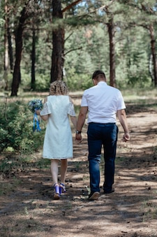 숲속 남자 소녀의 세련된 커플은 숲의 배경에 있는 큰 오래된 나무 아래에서 함께 껴안습니다.