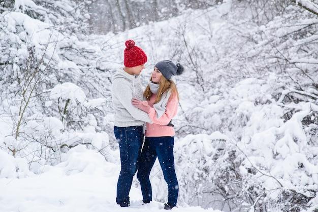 Стильная пара в вязаной одежде во время снегопада