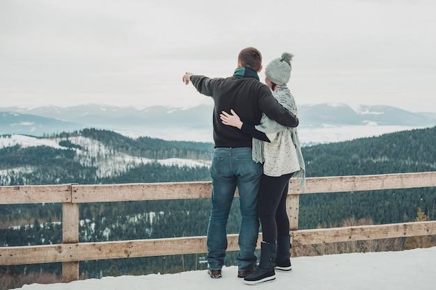 Стильная влюбленная пара, обнимая в заснеженных горах счастливая семья, нежно обнимая зимой горы и лес вид со спины