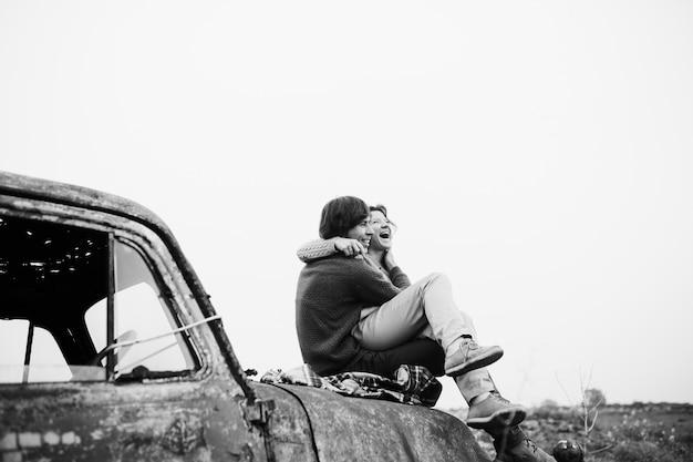 Стильная влюбленная пара сидит на заброшенном грузовике и выглядит счастливой