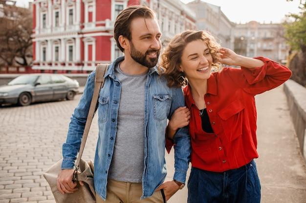 ロマンチックな旅行で通りを抱きしめて歩く愛のスタイリッシュなカップル