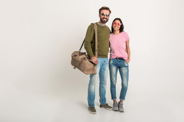ピンクのtシャツを着たスタイリッシュなカップルの孤立した、かなり笑顔の女性と旅行バッグを持って、ジーンズを着て、サングラスをかけて、一緒に楽しんでいるスウェットシャツの男性
