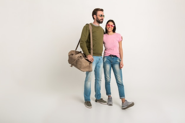 Stylish couple isolated, pretty smiling woman in pink t-shirt and man in sweatshirt holding travel bag, dressed in jeans, wearing sunglasses, having fun together