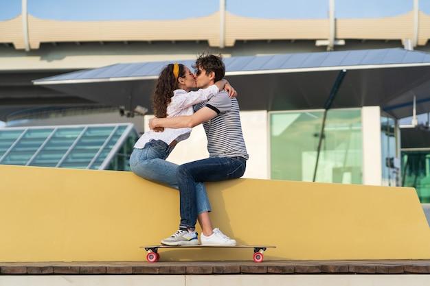 스케이트 파크에 앉아 있는 세련된 커플 키스 젊은 귀여운 롱보더 남자와 여자가 껴안고 있다
