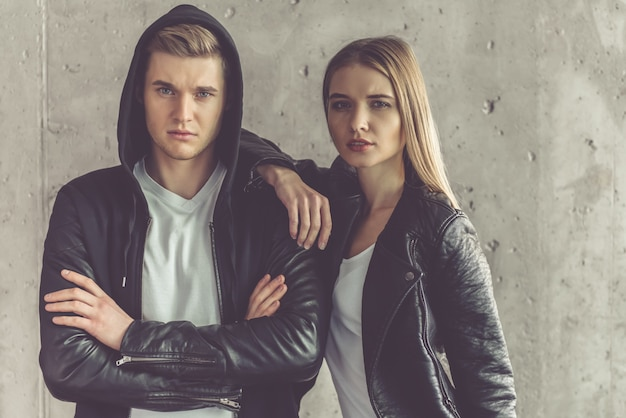 Stylish couple in leather jackets is looking at camera.