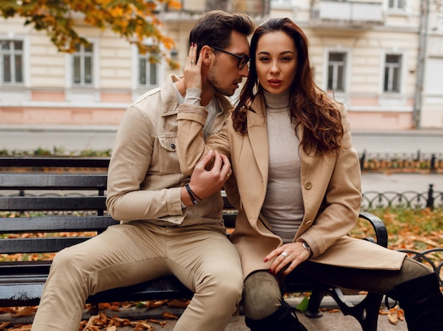 Stylish couple in love posing outdoor. autumn fashion trends. brunette model with stylish guy in beige coat sitting on bench.