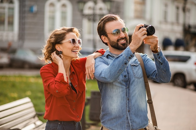 Stylish couple in love walking embracing in street on romantic trip and taking photo