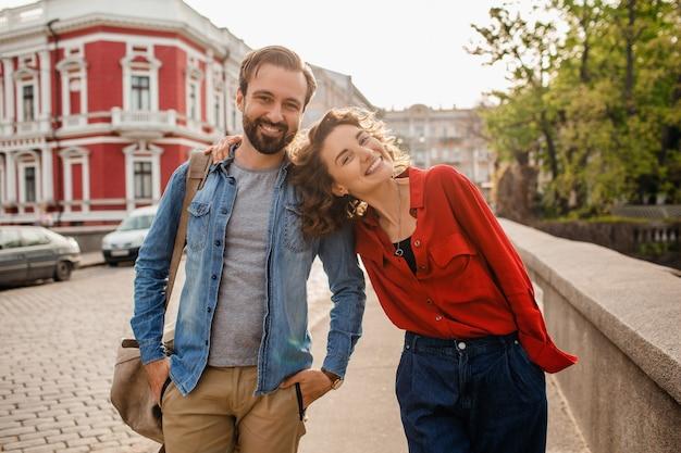 Elegante coppia innamorata che cammina abbracciata in strada durante un viaggio romantico