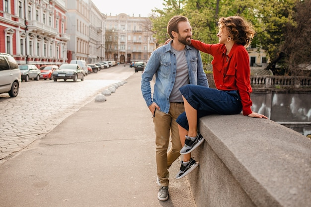 Stylish couple in love walking embracing in street on romantic trip