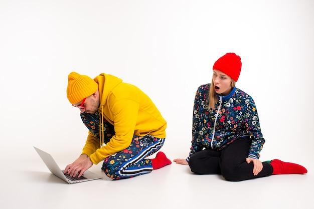 Стильная пара мужчина и женщина в яркой одежде, глядя на экран ноутбука над белой стеной
