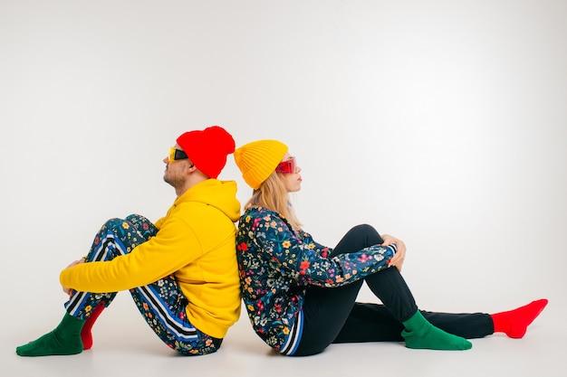 Стильная пара мужчина и женщина в красочной одежде позирует на белом фоне