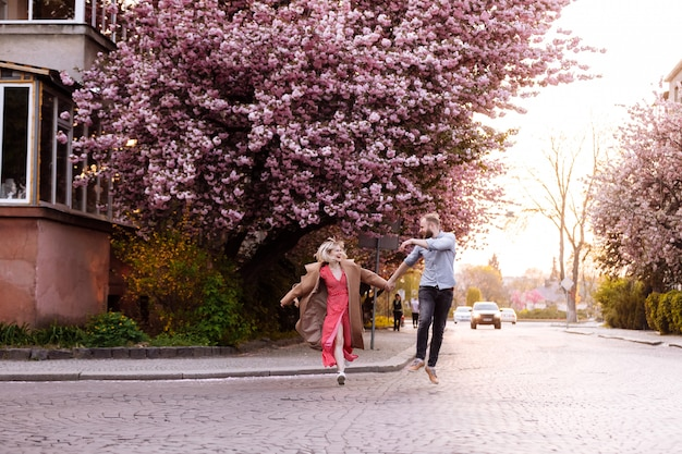 Stylish couple in the park with sakura tree with blooming pink flowers. beautiful young couple, man with beard and blonde woman having fun in the spring park.