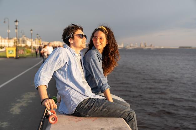 세련된 커플은 해변의 부두에 앉아 강이나 바다를 바라보며 일몰을 즐기는 행복한 남자와 여자