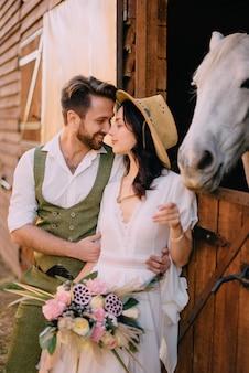 Стильная пара стоит и обниматься возле конюшни