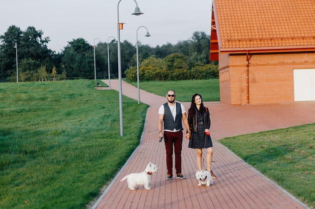 A stylish couple strolls through the park with two white dogs