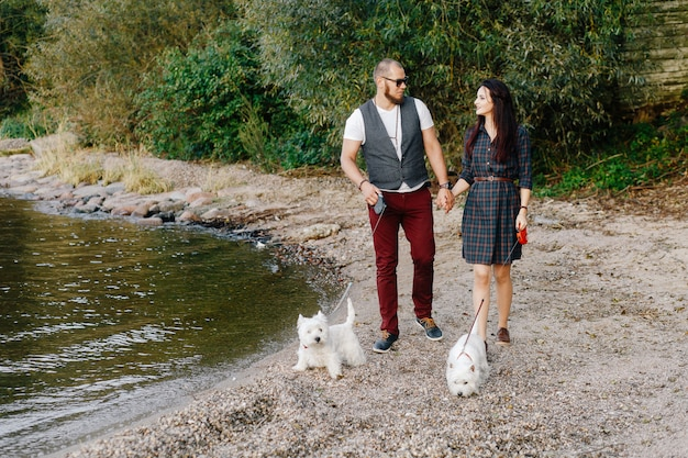 A stylish couple strolls through the park with white dogs