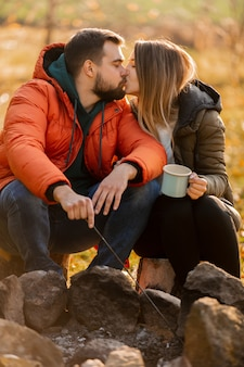 Stylish couple with cup of coffee near bonfire