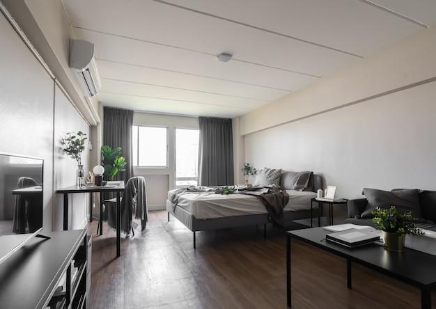 Стильная уютная спальня оформлена в современном минималистском стиле с мягкими подушками и красивым дизайном интерьера из серого тканевого дивана