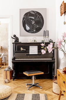 Stylish and cozy interior of living room with black piano, furniture, plant, wooden clock, lamp, mock up painitngs, carpet, decoration and elegant personal accessories in modern home decor