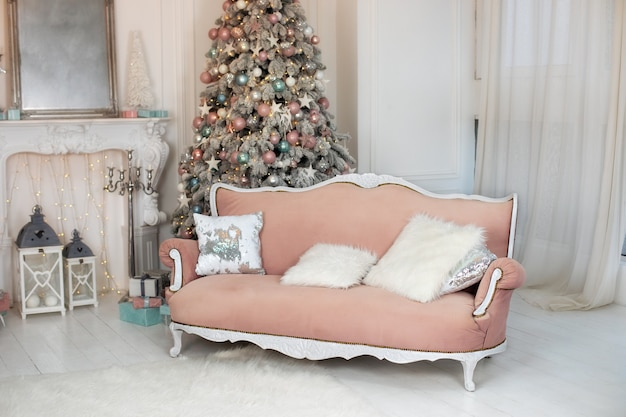 Stylish cozy interior of living room with pink sofa christmas tree and lights glowing garlands