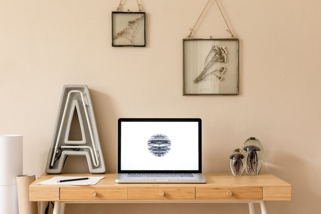 Stylish and creative wooden desk with laptop screen, photo frames, office accessories, plant and cement neon letter.