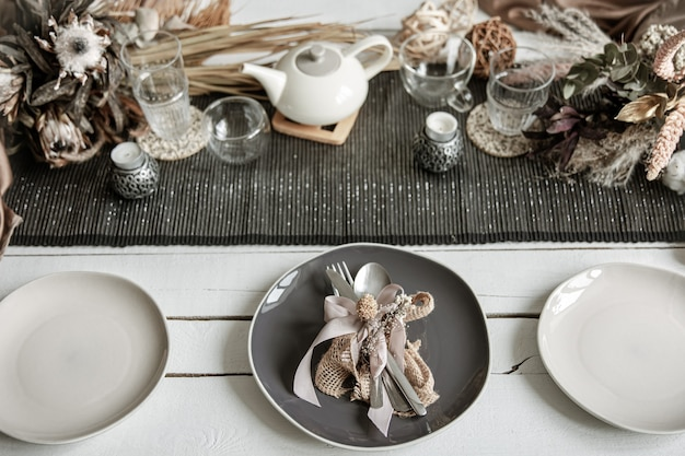 スカンジナビアスタイルの装飾的な要素を持つコーヒー色のセットテーブルのスタイリッシュな食器とカトラリー Premium写真