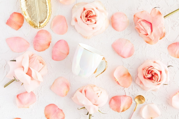Stylish cup of coffee, leaf golden plate and spoon with pink roses flowers and petals