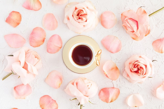 Stylish cup of coffee with pink roses flowers and petals