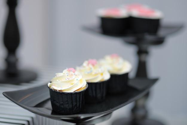 Stylish cupcakes on black glass plate